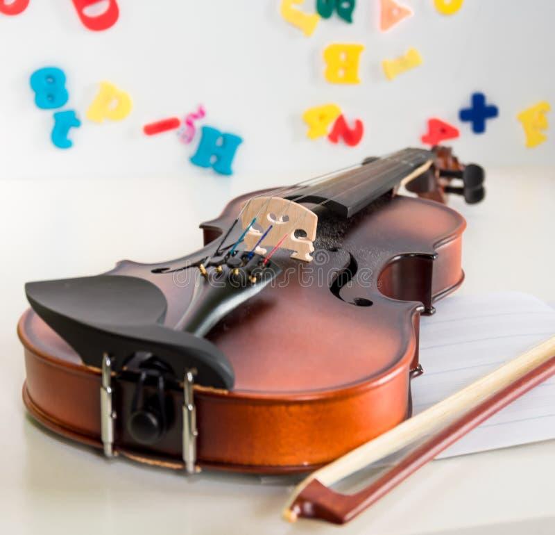 Chiuda su di un violino e di un arco del bambino, trovandosi su uno scrittorio bianco con il fondo vago del bordo bianco con le l fotografie stock libere da diritti