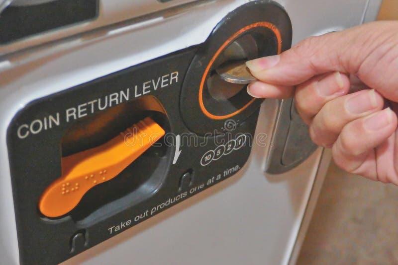 Chiuda su di una certa parte del distributore automatico con la leva di ritorno della moneta con la moneta della tenuta della man immagine stock