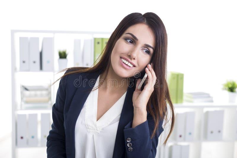 Chiuda su di una donna di affari sorridente sul suo telefono cellulare in un bianco immagini stock libere da diritti