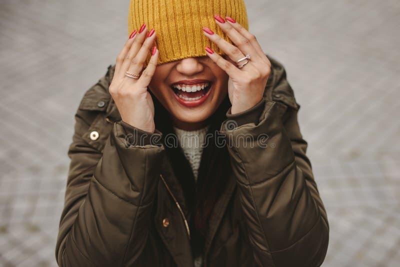 Chiuda su di una donna sorridente con il fronte parzialmente coperto immagini stock libere da diritti