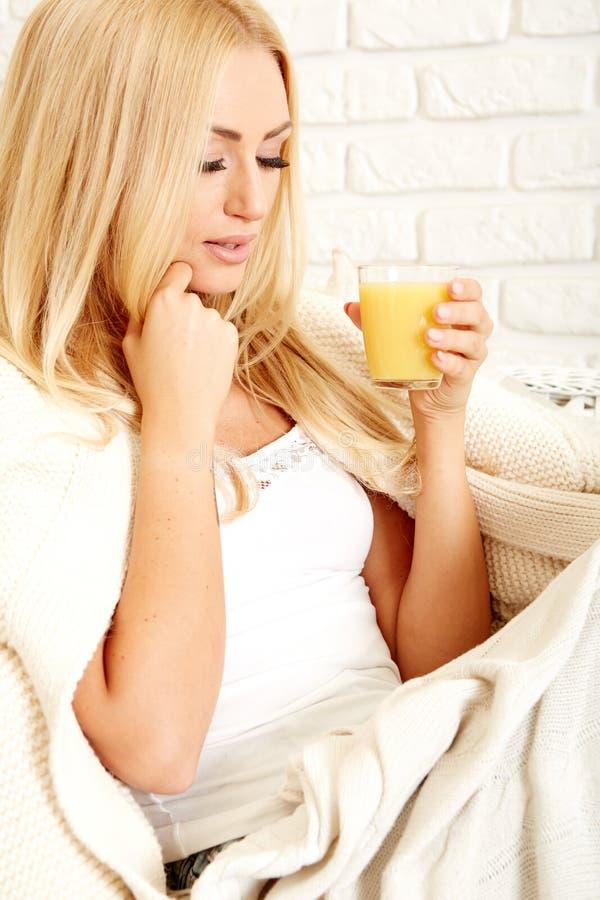 Chiuda su di una donna sorridente con succo d'arancia immagini stock