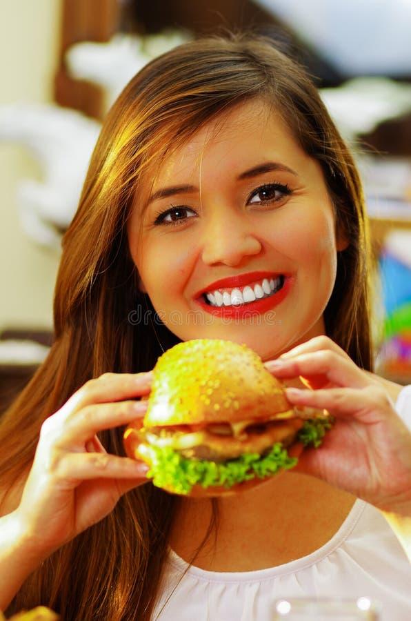 Chiuda su di una donna sorridente di bellezza in caffè che tiene un hamburger delizioso immagine stock libera da diritti