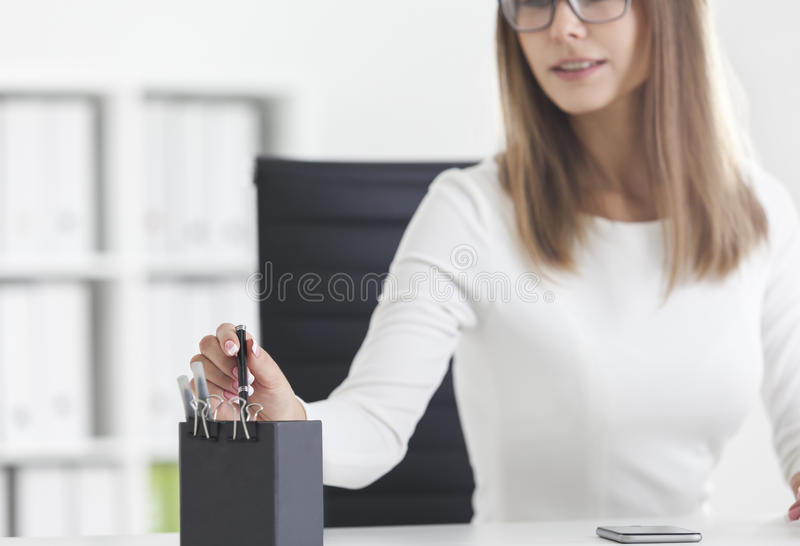 Chiuda su di una donna in vetri che prendono una penna fotografie stock libere da diritti