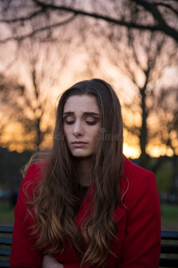 Chiuda su di una giovane donna turbata da solo nei suoi pensieri fotografia stock