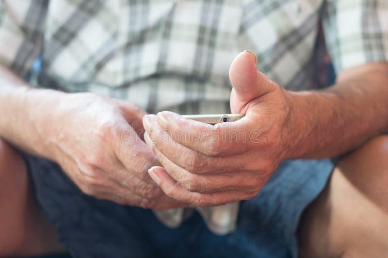 Chiuda su di una mano anziana dell'uomo facendo uso dello Smart Phone mobile fotografia stock libera da diritti