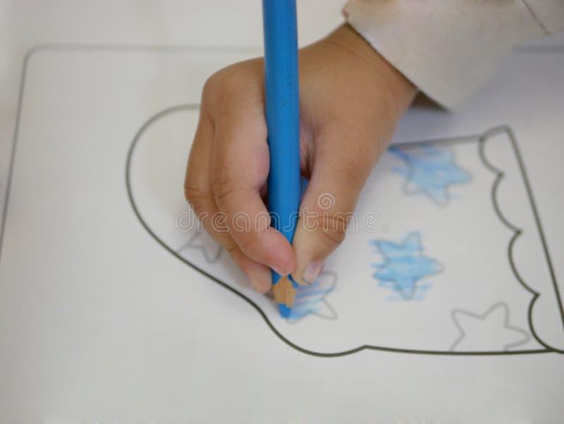 Chiuda su di una mano del ` s della neonata che tiene una matita di colore immagini stock