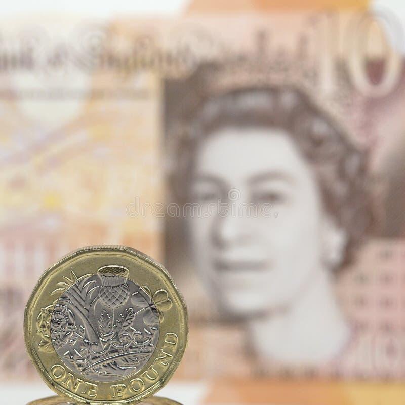 Chiuda su di una moneta da una libbra con un fondo della nota da dieci libbre - valuta britannica fotografia stock libera da diritti