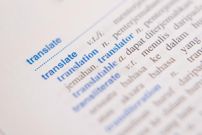 Chiuda su di una parola della TRADUZIONE in un dizionario fotografia stock