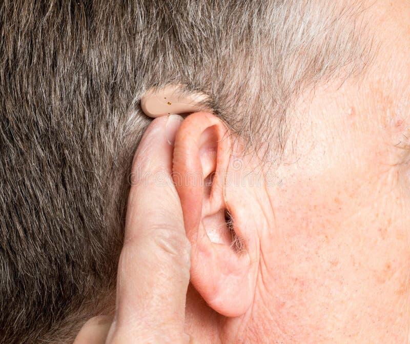 Chiuda su di una protesi acustica moderna minuscola dietro l'orecchio immagini stock libere da diritti