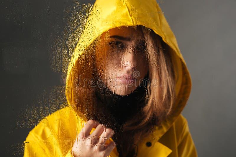 Chiuda su di una ragazza triste vestita in impermeabile immagine stock libera da diritti
