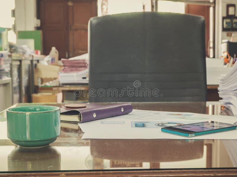 Chiuda su di una tazza di caffè e dei documenti di affari fotografia stock libera da diritti