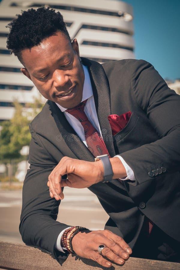 Chiuda su di uno giovane e dell'uomo d'affari nero attraente che passa attraverso un passaggio pedonale e che parla per telefono  fotografia stock libera da diritti