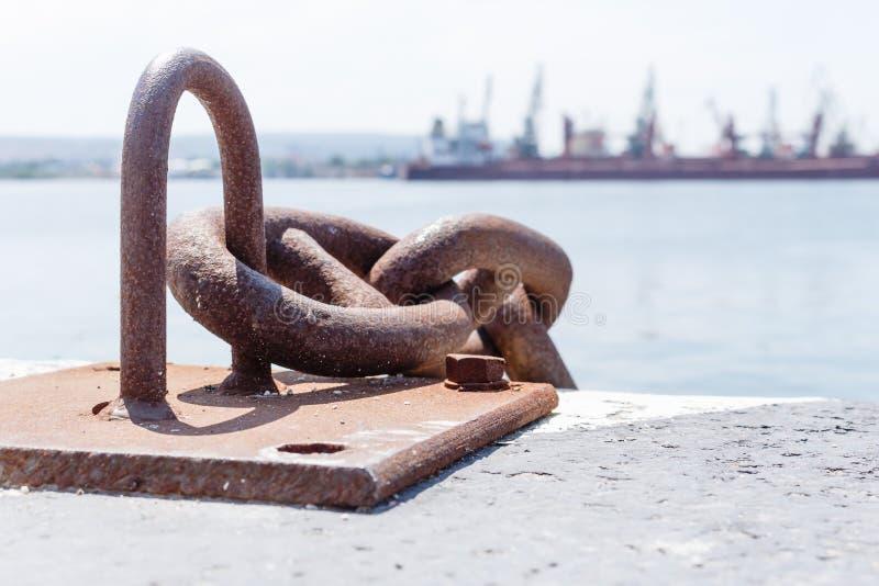 Chiuda su di vecchia catena arrugginita, il porto industriale con le navi, fondo della gru sfuocato, il giorno soleggiato, concet fotografia stock