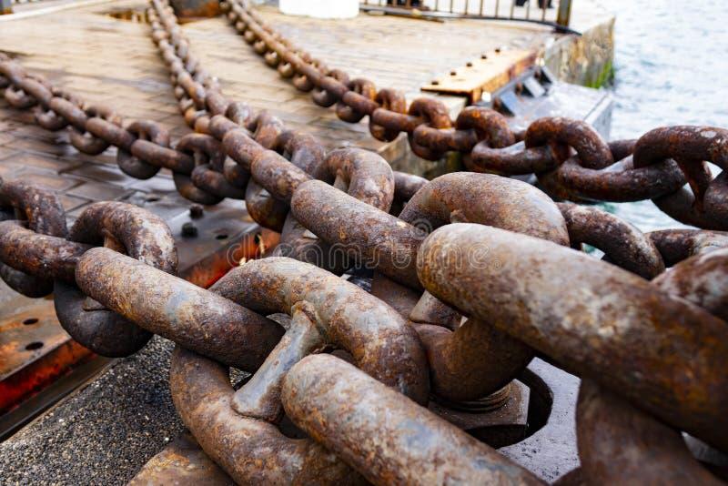 Chiuda su di vecchia catena arrugginita, porto industriale con le catene fotografie stock libere da diritti