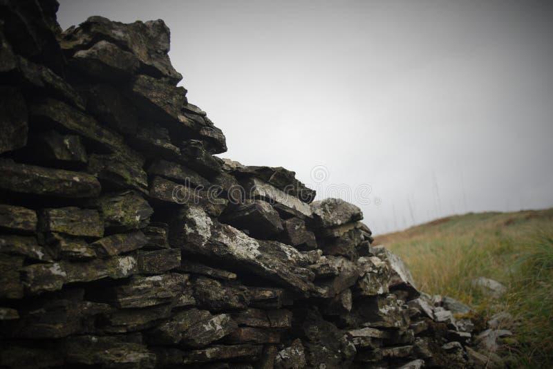 Chiuda su di vecchia parete di pietra ripartita immagine stock libera da diritti
