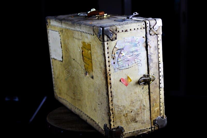Chiuda su di vecchia valigia utilizzata isolata con i ribattini, la presa di cuoio e le serrature a combinazione fotografia stock