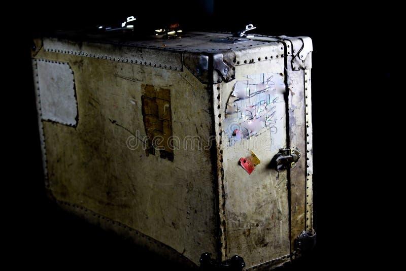Chiuda su di vecchia valigia utilizzata isolata con i ribattini, la presa di cuoio e le serrature a combinazione immagine stock