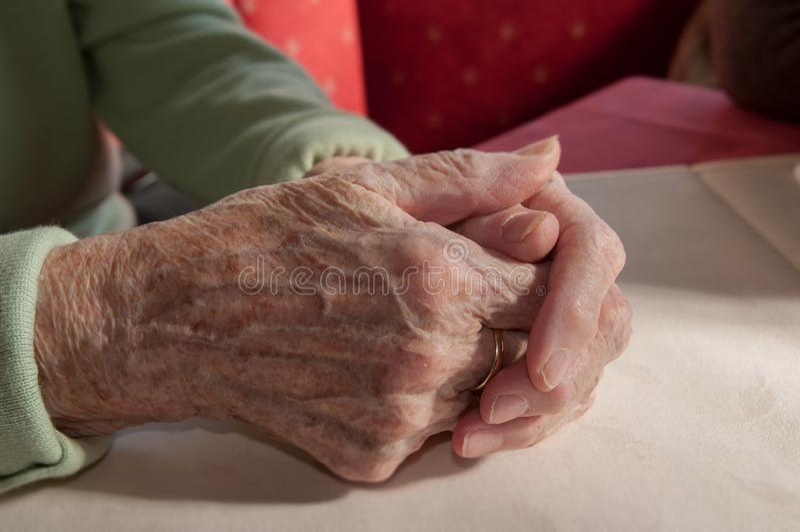 Chiuda su di vecchie mani piegate della donna senior immagini stock libere da diritti