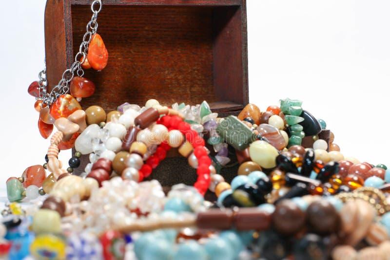 Chiuda su di vecchio contenitore di gioielli con le multi perle colorate su fondo bianco immagini stock