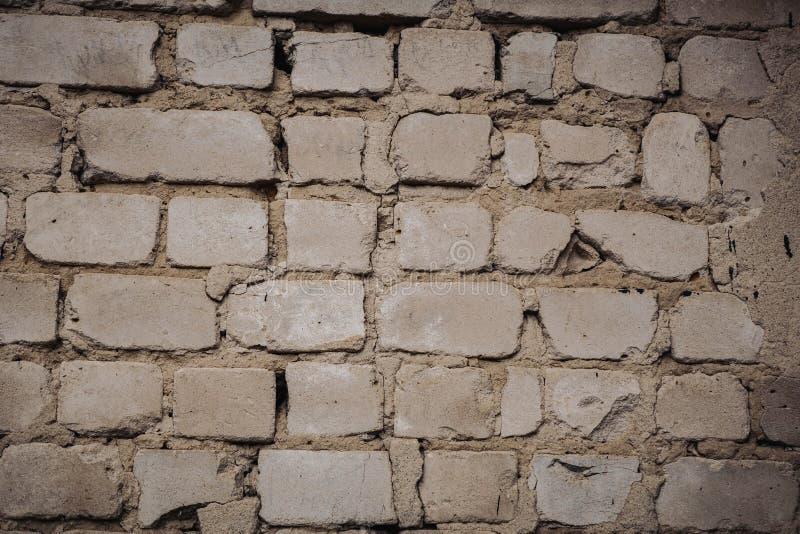 Chiuda su di vecchio muro di mattoni esteriore con pittura bianca macchiata e di pelatura fotografia stock