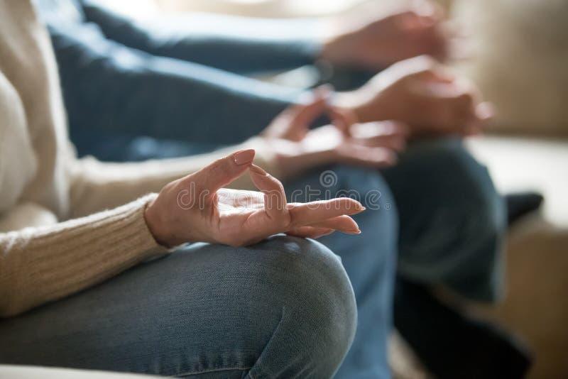 Chiuda su di yoga invecchiata di pratica delle coppie a casa fotografie stock