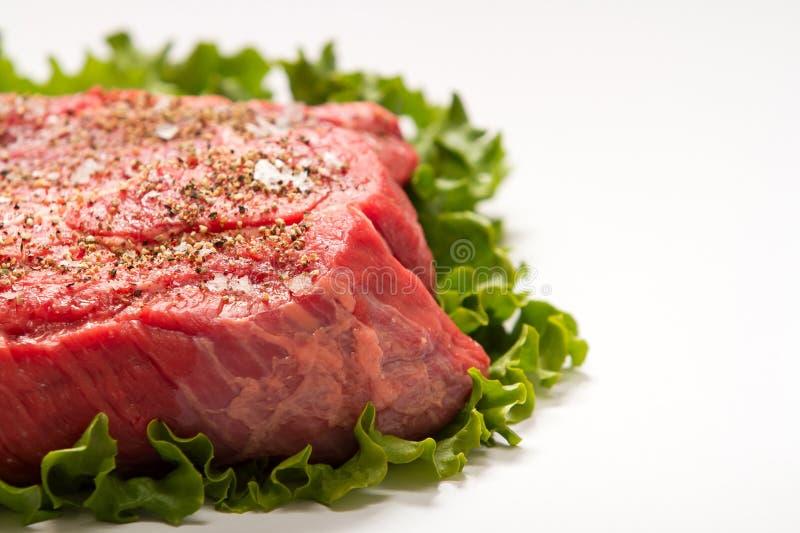 Chiuda su esperta bistecca cruda sulla lattuga di foglia verde fotografia stock libera da diritti