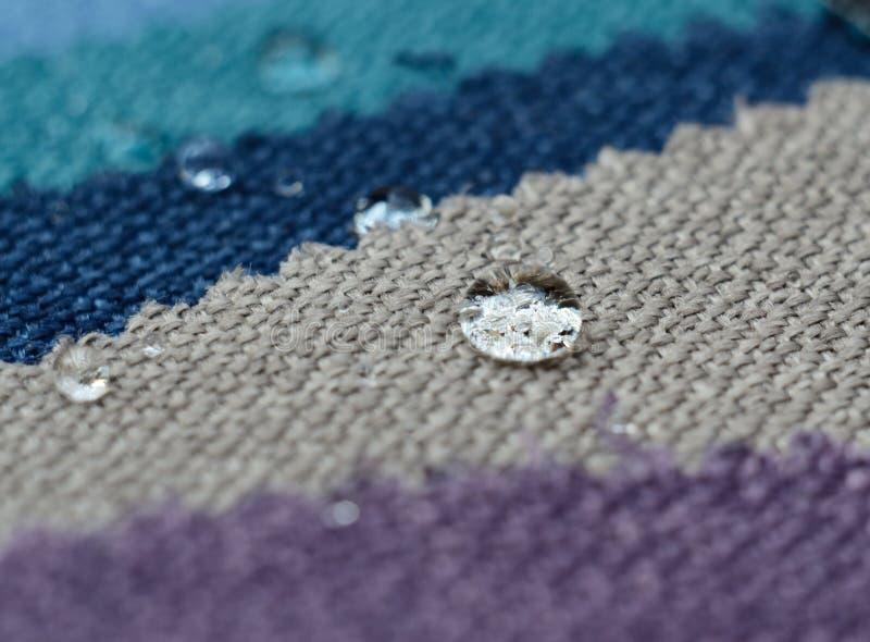 Chiuda su goccia di acqua sui campioni del tessuto dell'iuta Concetto per le superfici pulite e impermeabili facili immagine stock