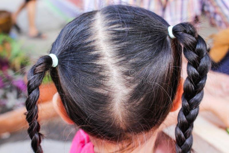 Chiuda su indietro della testa asiatica del bambino con capelli intrecciati immagini stock libere da diritti