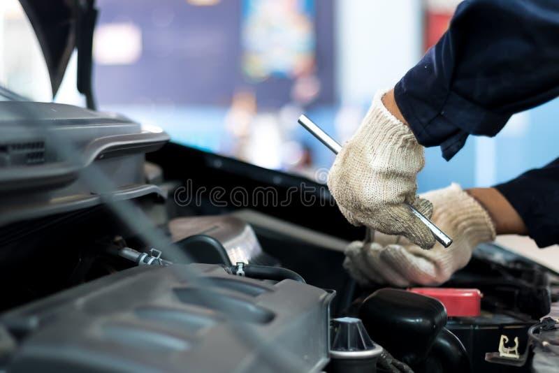 Chiuda su, la gente è la riparazione un uso dell'automobile una chiave e un cacciavite lavorare fotografie stock