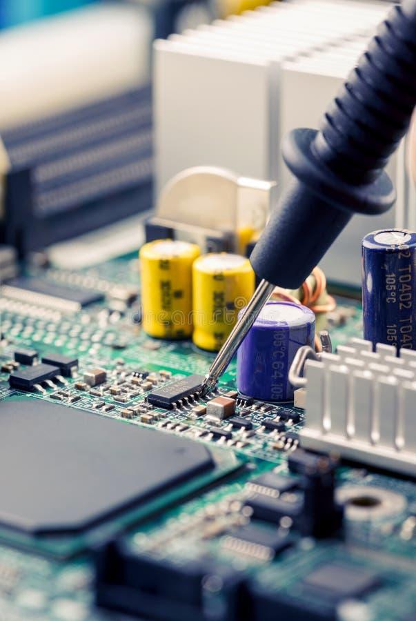 Chiuda su - la scheda madre di misurazione del circuito del computer del multimetro dell'ingegnere del tecnico fotografie stock
