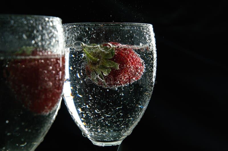 Chiuda su, macro Fragole rosse succose che galleggiano in una bevanda circondata dalle bolle Copi lo spazio fotografia stock libera da diritti