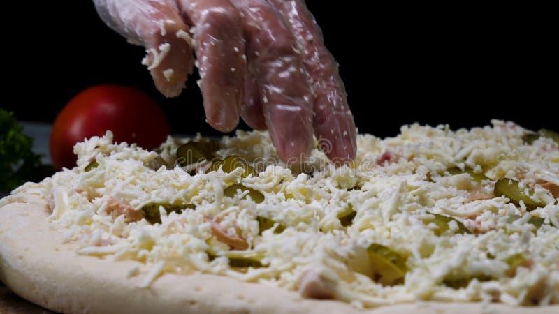 Chiuda su per il processo di produrre la pizza dalle mani del cuoco unico isolate sul fondo nero Pagina Allineando lo strato del  fotografie stock