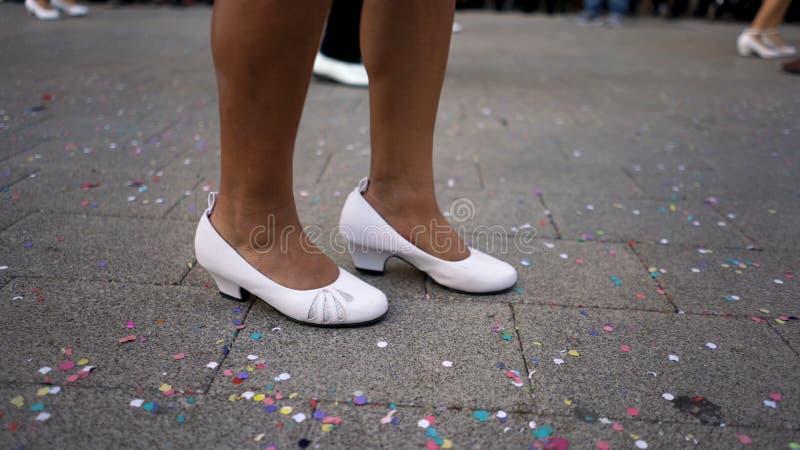 Chiuda su per le gambe degli uomini e delle donne in scarpe bianche che ballano nella via durante la festa nazionale Arte spagnol fotografia stock