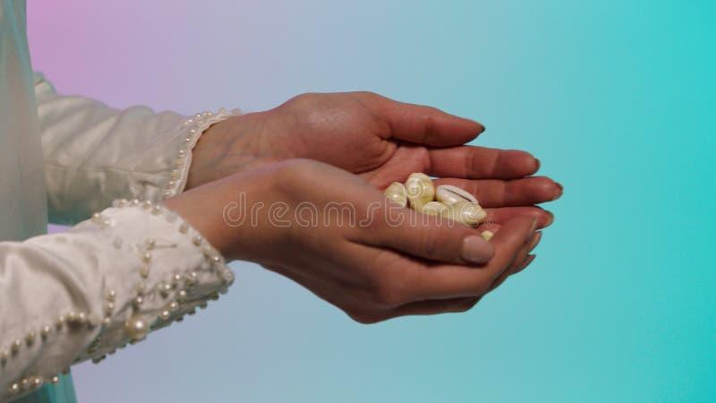 Chiuda su per le mani orientali della giovane donna che danno molte piccole conchiglie alle mani dell'uomo, concetto di baratto a fotografia stock libera da diritti