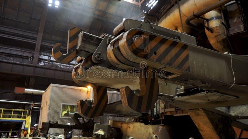 Chiuda su per lo scivolo metallurgico alla fabbrica d'acciaio, concetto dell'industria pesante Ganci giganti dello scivolo per immagine stock libera da diritti