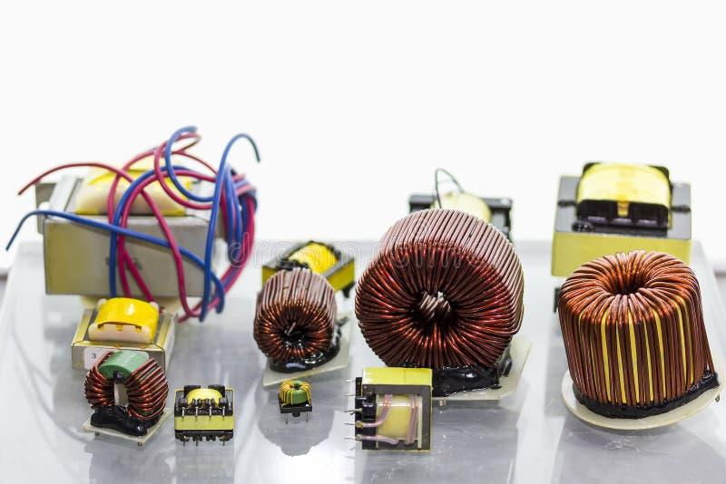 Chiuda su piccolo dei molti la bobina ed il trasformatore elettrico per l'industriale con lo spazio della copia immagini stock libere da diritti