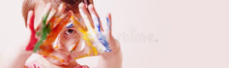 Chiuda su poca ragazza sveglia con il trucco variopinto dei bambini che mostra le mani dipinte Concetto felice di arte e di infan immagine stock