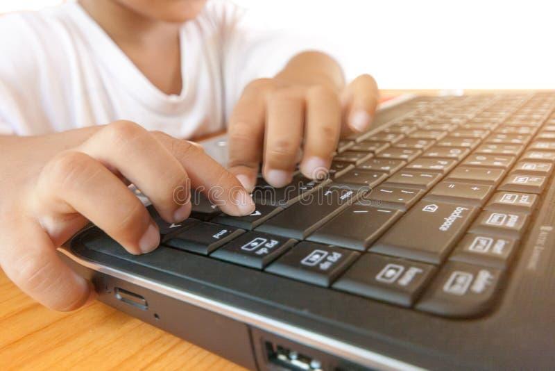 Chiuda su poco ragazzo asiatico facendo uso del pc del computer portatile per l'apprendimento, l'istruzione e giocante della tecn fotografia stock
