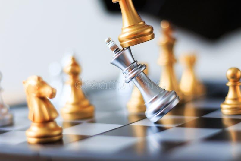 Chiuda su scacchi dorati del colpo per sconfiggere gli scacchi d'argento o di re di uccisione immagini stock