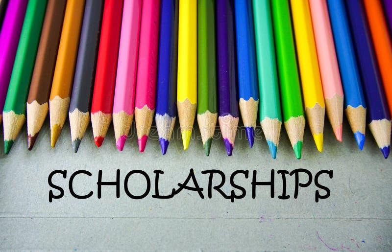 Chiuda su scrittura colorata della matita con le BORSE DI STUDIO Concetto di formazione fotografie stock libere da diritti