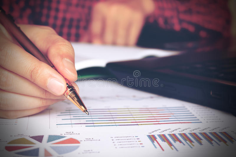 Chiuda su scrittura della mano del giovane con la calcolazione ed usando del lapto fotografie stock