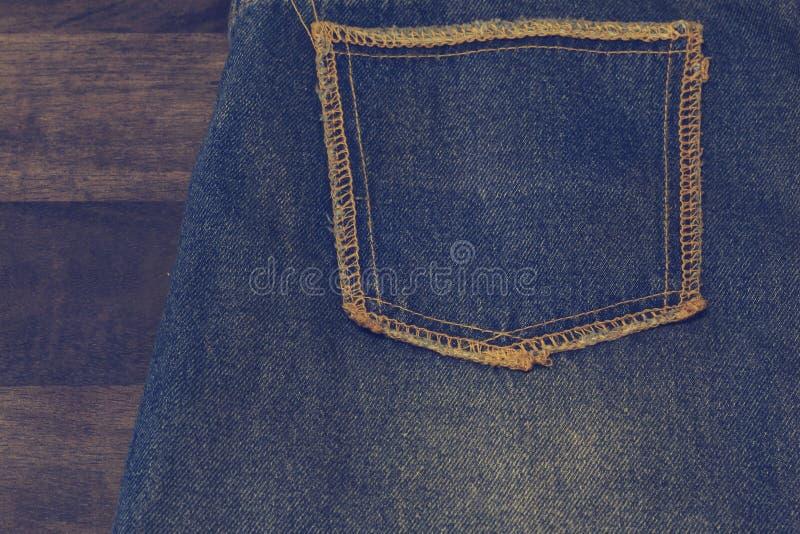 Chiuda su su della tasca delle blue jeans lavata immaginazione Sul fondo di struttura di legno di quercia, jeans strappati di uno immagini stock