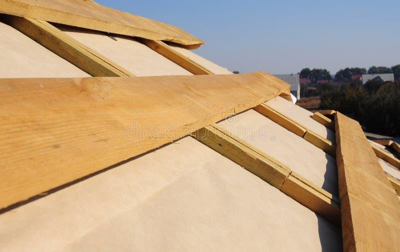 Chiuda su sui fasci di legno del tetto, le travi, capriate con l'installazione d'impermeabilizzazione della membrana fotografia stock
