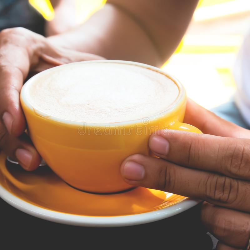 Chiuda su sul caffè caldo del latte in tazza gialla in mani dell'uomo fotografia stock libera da diritti