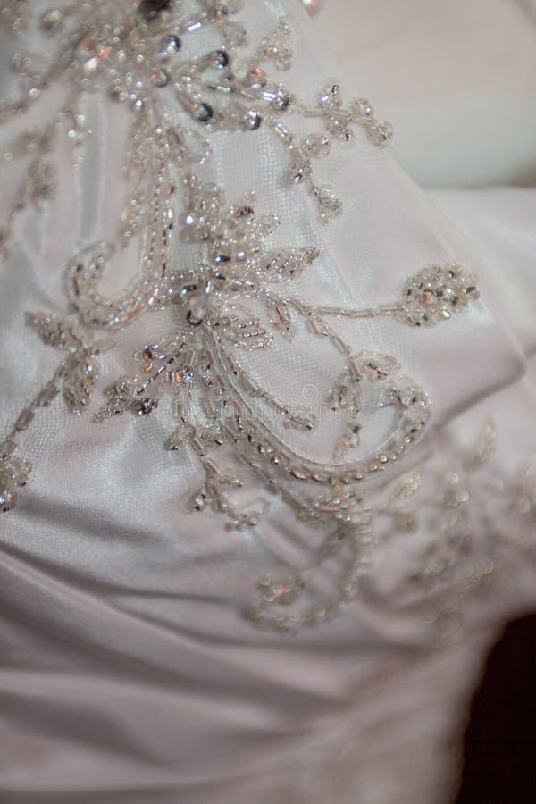 Chiuda su sul dettaglio dell'abito di nozze immagini stock libere da diritti