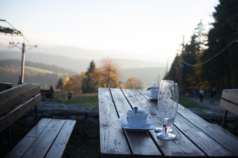 Chiuda su sul vetro del caffè e della birra sulla tavola in montagna fotografie stock