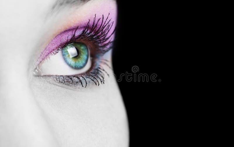 Chiuda in su sull'occhio femminile con variopinto compongono fotografia stock