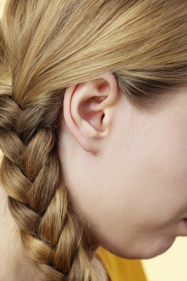 Chiuda su sull'orecchio e sui capelli femminili della treccia immagine stock libera da diritti