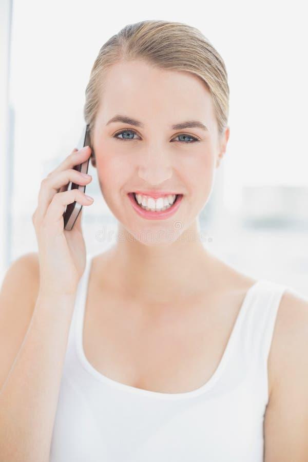 Chiuda su sulla donna sportiva felice che ha una telefonata fotografia stock