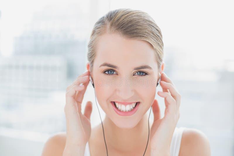 Chiuda su sulla donna sportiva sorridente che ascolta la musica immagini stock libere da diritti